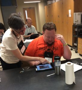 Photo of mini workshop presenter working with attendee on an iPad